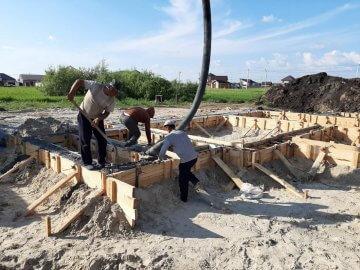 Бригада строителей возводит ленточный фундамент